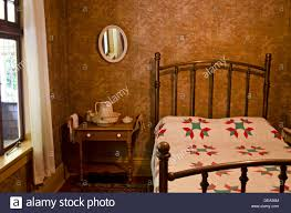 vintage old fashioned bedroom setting with iron bed frame and wash stock photo vintage old fashioned bedroom setting with iron bed frame and wash basin hand made quilt on the bed