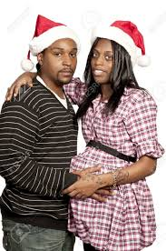 a beautiful young black couple wearing christmas santa hats stock