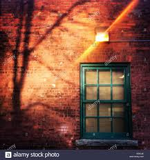 light brick sets side of a building as sun sets onto a brick wall and a green window