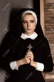 humble beautiful in robes holding a cross on a grey