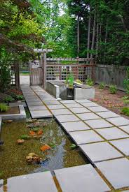 exterior design concrete paving with small plants and wood fence