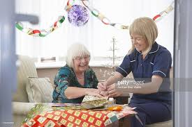 elderly gifts carer helping elderly woman wrap christmas gifts stock photo