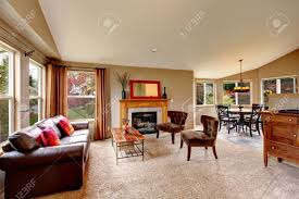 bright living room with beige carpet floor leather couch coffee
