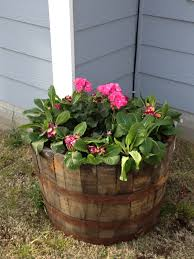 whiskey barrel planter bottom filled with plastic bottles so its