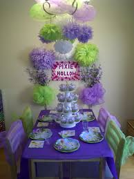 tinkerbell party ideas tulle on chandelier purple and green pom poms hanging everywhere