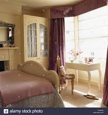 cream fitted wardrobe with interior drapes in traditional bedroom