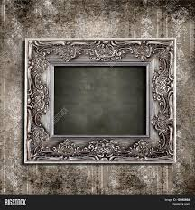 intricate old frame hanging on grungy vintage wallpaper stock