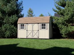 light brown maxibarn storage building in a backyard with pine