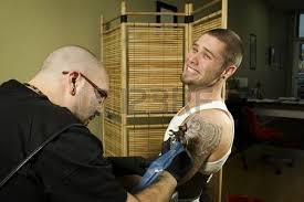 client in pain getting a tattoo stock photo picture and royalty