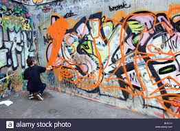 spray painting graffiti on concrete wall south bank london stock