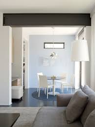rho architects exposed steel beam dining area grey sofa white