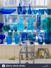 collection of blue glassware on shelving in bathroom stock photo