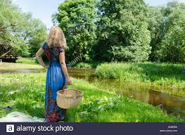woman with long blue dress standing with wicker basket in meadow