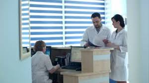 Hospital Reception Desk Young Doctor Talking With Patient At Hospital Reception Desk Stock