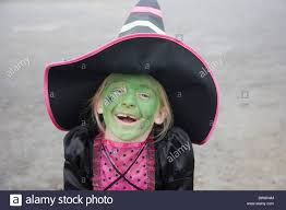 young child wearing halloween witches costume and face