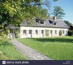 path across lawn to single storey french country house with attic