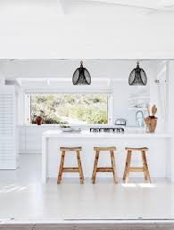gravity home white kitchen with wooden bar stooles in a seaside