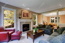 cozy living room with fireplace green sofas and red leather