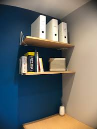 bureau de designer des étagères tenues par des équerre de designer au dessus d un