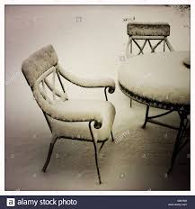 garden furniture under snow in a west texas backyard stock photo