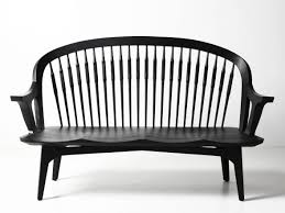 black wooden bench with curving back and bars on it combined with