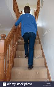 Walking Up Stairs With Crutches by Everyday Scene Of A Senior Woman Walking Up Stairs Holding Onto A