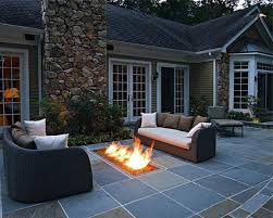 grey concrete floor patio with stone fire pit and chair ideas on