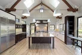 sleek modern kitchen with large marble island and skylights stock