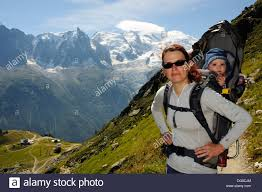 child in french a mother hiking in the french alps carrying her child in a baby