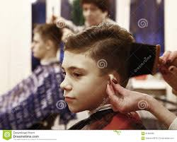 boy has his hair cut in barber shop men room editorial image