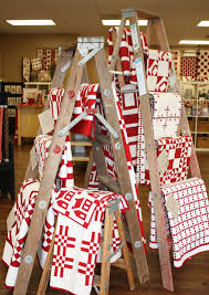 red and white quilts displayed on old wooden ladders booth