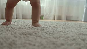 closeup of barefoot baby crawling on soft shag rug on the floor in