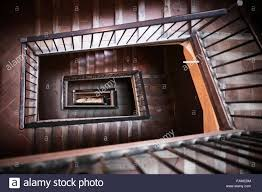 spiral rectangular staircase with wood and tile steps in housing