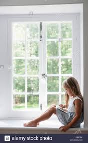 a young girl sitting at a window seat using a digital tablet a young girl sitting at a window seat using a digital tablet