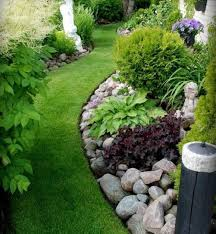 cozy frontyard with small plants also flowers plus grass and rock