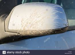 mud stained car wing mirror in blue metallic paint with dry mud