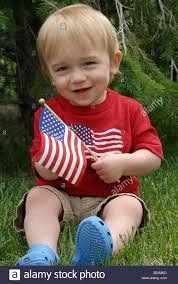 A American Flag Pictures A Baby Boy Sits In The Grass Waving An American Flag On The Fourth