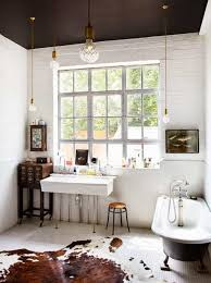 eclectic bathroom interior with clawfoot tub and hanging lights in