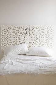 snow white bedroom accented by a wrought iron headboard
