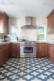 this kitchen pops with the combination of the red tile floor and