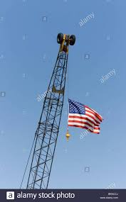 american flag hanging from the cable on the boom of a crane stock