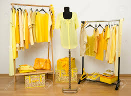 wardrobe full of all shades of yellow clothes shoes and