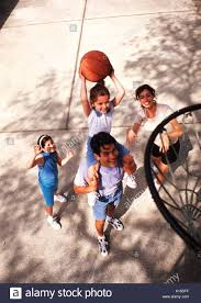 hispanic family basketball together outdoors at home stock