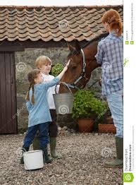 mother and kids feeding horse outside stable royalty free stock