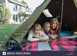 portrait mother and daughters with digital tablet in backyard tent
