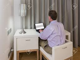 modern white computer desk senior man at modern white table desk and two chairs in hotel
