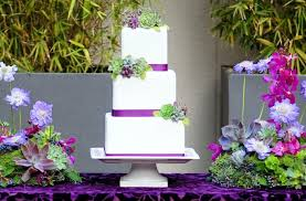 white wedding cake with pink purple and green details