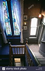 white lace curtains on tall stained glass window on dark landing