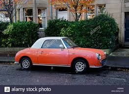 nissan orange orange coloured nissan figaro car parked in edinburgh stock photo