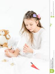 little in pajamas and curlers applying nail polish to